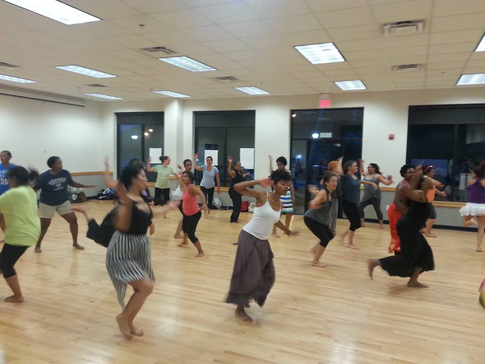 A dance studio full of people of all races and ages in an Afro Cuban dance class with live drumming.