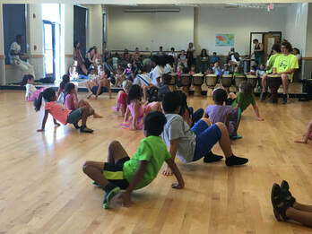 A dance studio of young children on the floor with one hand in the air practicing Capoeria with a teacher and traditional live music.