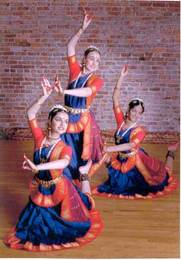 Three dancers in traditional Indian performance attire showing a traditional dance pose.