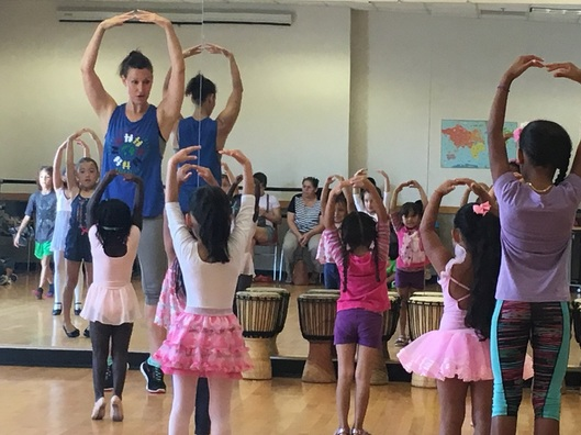 A children's ballet class with a diverse studio of children practicing piles.