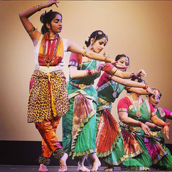 Four Indian dancers in performance attire posing during a Southern Indian dance.