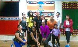 A diverse group of adult women posing after participating in a Zumba class.