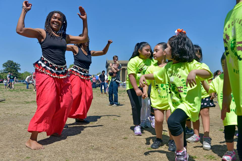 Global Education Center's Afro Latin adult dance troupe are dancing with some Latino children at Bicentennial Park during a community outreach.