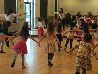 A dance studio full of young girls following a dance teacher who is showing them how to raise one leg behind them and move their torso forward.