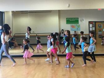 Three young girls, one in a pink tutu, another in a multicolor tutu and the other in workout clothing, are all practicing dance moves.